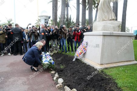 """President of the French far-right Front National (FN) party Marine Le Pen (L) and vice president of the FN party and mayor of Henin-Beaumont Steeve Briois (unseen), stand guard after placing a spray of flowers under the statue of """"Joan of Arc Jeanne D'Arc during a May Day rally in honour of the French historical figure, in Cannes"""