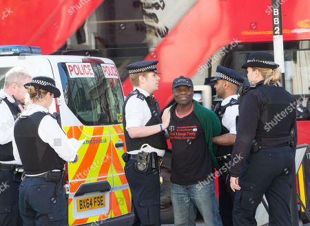Supporter of Justice for Ezeugo family is arrested after demonstrating with a banner inside the High Court.The Ezeugo family are claiming 23 years of police harassment and have written to Lord Justice Sir Brian Leveson.
