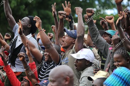 Supporters of the Opposition leader Raila Odinga acknowledge his greetings when he rose to speak during this year's Labour Day celebrations at Uhuru Park in Kenya's capital Nairobi.