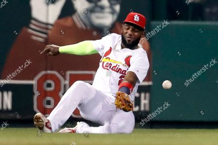 St. Louis Cardinals left fielder Marcell Ozuna is unable to catch a two-run double by Chicago White Sox's Yoan Moncada during the fourth inning of a baseball game, in St. Louis