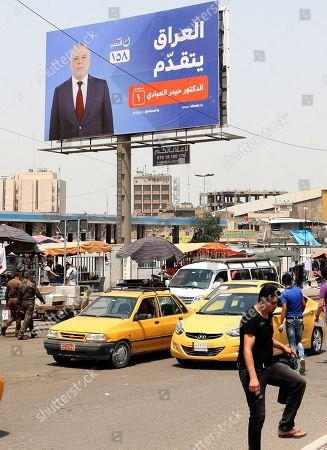 Iraqis walk next to an election campaign poster for the Iraqi prime minister Haider al-Abadi at Tahrir square in central Baghdad, Iraq, 02 May 2018. Iraqi political blocs are preparing for the upcoming parliament elections scheduled on 12 May.