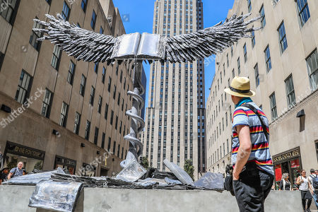 Uraeus, the first outdoor public sculpture by artist Anselm Kiefer is seen at Rockefeller Square near Fifth Avenue in Manhattan in New York City on Wednesday, 02. The work is on display until July 22. The Ureaus, presented by Gagosian and organized by the Public Art Fund and Tishman Speyer, consists of a giant open book with eagle wings 30 feet long, made entirely of lead, on top of a 20-foot-high stainless steel column . Grouped around the base of the spine are even larger lead books, while a large snake coils the spine. Lead is one of the artist's preferred materials for its fluid and soft properties traditionally associated with alchemical transformation, especially its second stage: dissolution.  (Photo: William Volcov)
