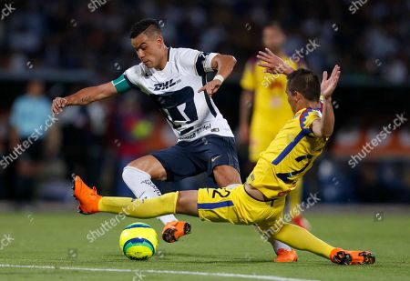Pumas' Pablo Barrera, left, fights for the ball with America's Paul Aguilar during a Mexican soccer league quarterfinals match in Mexico City