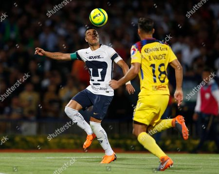 Pumas' Pablo Barrera, left, fights for the ball with America's Bruno Valdez during a Mexican soccer league quarterfinals match in Mexico City