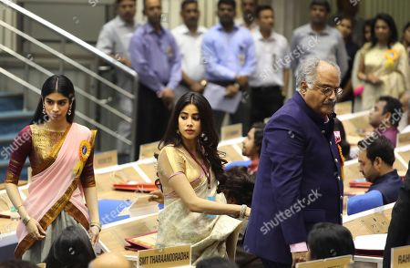 Bollywood actress Sridevi's husband Boney Kapoor, right, and daughters Janhvi Kapoor, center, and Khushi Kapoor walk to receive the best actress award conferred posthumously to Sridevi at the 65th National Film Awards ceremony in New Delhi, India