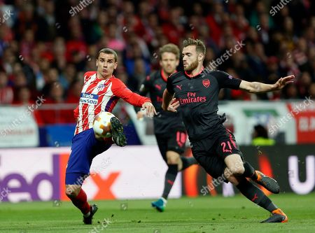 Atletico's Antoine Griezmann, left, duels for the ball with Arsenal's Calum Chambers during the Europa League semifinal, second leg soccer match between Atletico Madrid and Arsenal at the Metropolitano stadium in Madrid, Spain