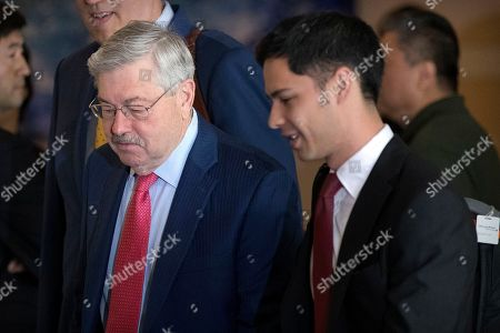U.S. Ambassador to China Terry Branstad, left, leaves a hotel in Beijing, . Chinese and U.S. officials met face-to-face Thursday to try and resolve a dispute over technology that has taken the world's two largest economies the closest they've ever come to a trade war