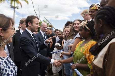 French President Emmanuel Macron (L) shakes hands as he visits with students at Michel Rocard high school
