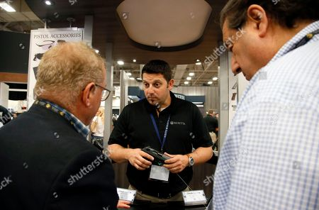Scott Shepherd, of Beretta USA Corp., shows a pistol to attendees at the National Rifle Association convention in Dallas