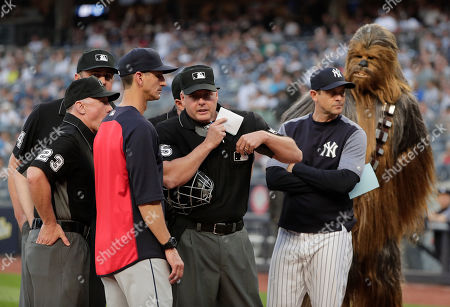 Home plate umpire Tim Timmons, center, goes over rules and boundaries with New York Yankees manager Aaron Boone and Cleveland Indians major league coach Mark Budzinski as Star Wars character Chewbacca looks during Star Wars night before a baseball game against the Cleveland Indians at Yankee Stadium, in New York