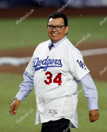 Retired Major League Baseball pitcher Fernando Valenzuela smiles as he walks to make the first pitch during the regular-season major league baseball game between the San Diego Padres and the Los Angeles Dodgers in Monterrey, Mexico