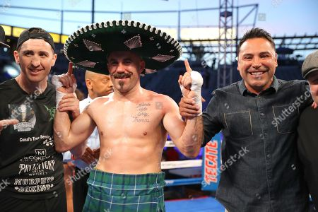 Gary O'Sullivan celebrates with trainer Paschal Collins (left) and Oscar De La Hoya of Golden Boy Promotions