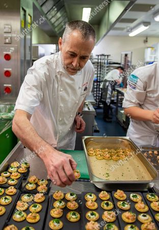 Stock Picture of Michel Roux Jr plates up caviar and smoked salmon canapes for service in the Chez Roux restaurant