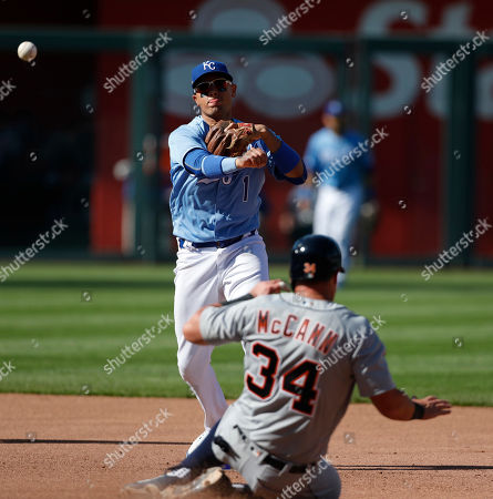 Detroit Tigers' James McCann (34) slides into a double play as Kansas City Royals second baseman Ryan Goins (1) throws to first in the sixth inning of a baseball game at Kauffman Stadium in Kansas City, Mo., . Julio Iglesias was out at first