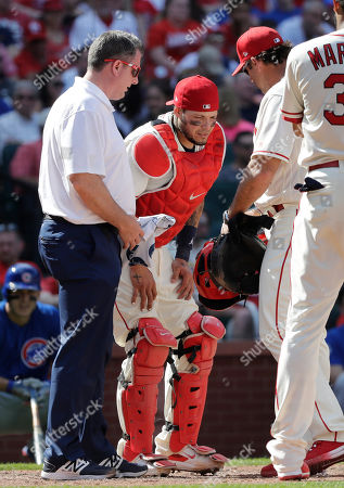 Chris Conroy, Yadier Molina, Mike Matheny. St. Louis Cardinals trainer Chris Conroy, left, and manager Mike Matheny, right, attend to catcher Yadier Molina after Molina was injured on a pitch during the ninth inning of a baseball game against the Chicago Cubs, in St. Louis