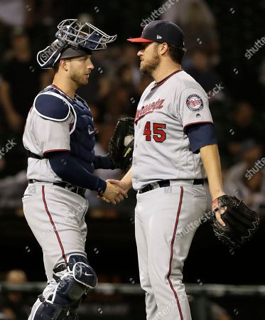 Phil Hughes, Mitch Garver. Minnesota Twins relief pitcher Phil Hughes, right, celebrates with catcher Mitch Garver after they defeated the Chicago White Sox in a baseball game, in Chicago
