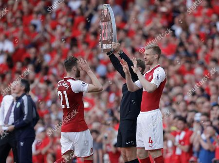 Arsenal's Per Mertesacker, right, clasps hands with teammate Calum Chambers as he replaces him during the English Premier League soccer match between Arsenal and Burnley at the Emirates Stadium in London, . The match is Arsenal manager Arsene Wenger's last home game in charge after announcing in April he will stand down as Arsenal coach at the end of the season after nearly 22 years at the helm