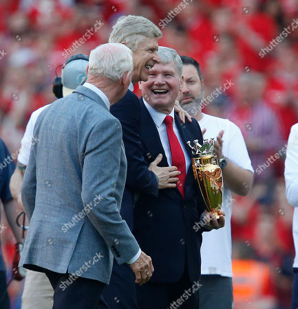 Stock Picture of Arsene Wenger is presented by Pat Rice and Bob Wilson the Gold Premier League Champions Trophy, won when Arsenal went the entire 2003/2004 season undefeated, which was given to him upon leaving the club