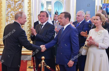 Russian President-elect Vladimir Putin (L) shakes hands with Russian Prime Minister Dmitry Medvedev (front 2-R) as Medvedev's wife, Svetlana Medvedeva (R) and former German Chancellor and Chairman of the Board of Directors of Rosneft, Independent Director, Gerhard Schroeder (2-L) applaud during an inauguration ceremony of Vladimir Putin as Russian President in the Kremlin, in Moscow, Russia, 07 May 2018. Vladimir Putin won his fourth term in the Kremlin during presidential elections on 18 March 2018.