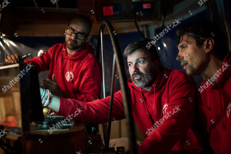 Stock Picture of Spanish NGO Proactiva Open Arms head of mission Riccardo Gatti, center, and chief engineer Savvas Kourepinis, watch the radar for migrant boats with Italian Parliamentary Riccardo Magi, right, as they navigate on international waters near Libya, . A Spanish nonprofit dedicated to helping migrants at sea says it is still waiting for authorization to transfer 105 migrants it rescued over 24 hours ago in waters north of Libya during a mission Sunday
