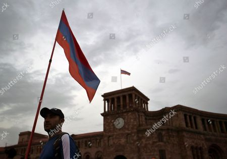 Armenian man stands with a state flag ahead of a concert to support the opposition lawmaker Nikol Pashinian in Yerevan, Armenia, . Nikol Pashinian, who led weeks of protests that attracted tens of thousands of people and forced Serzh Sargsyan to resign as premier, is expected to be chosen as prime minister by parliament Tuesday
