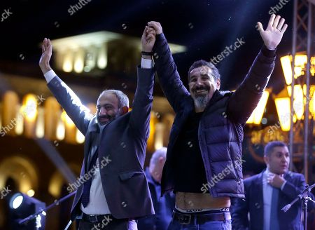 The Armenian-American singer Serj Tankian of System of a Down, right, and opposition lawmaker Nikol Pashinian greet fans during a concert in Yerevan, Armenia, . Nikol Pashinian, who led weeks of protests that attracted tens of thousands of people and forced Serzh Sargsyan to resign as premier, is expected to be chosen as prime minister by parliament Tuesday