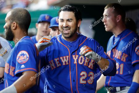 New York Mets' Adrian Gonzalez celebrates in the dugout after hitting a solo home run off Cincinnati Reds relief pitcher Jackson Stephens in the fifth inning of a baseball game, in Cincinnati
