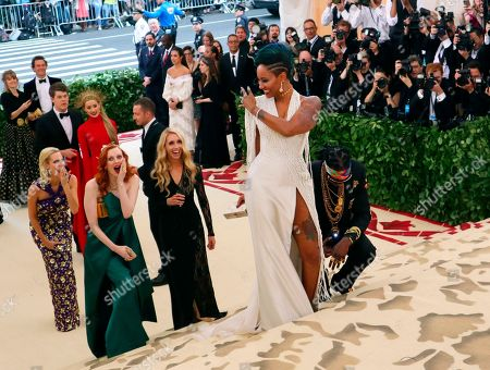 2 Chainz, kneeling center, and Kesha Ward, standing center, arrive at The Metropolitan Museum of Art's Costume Institute benefit gala celebrating the opening of the Heavenly Bodies: Fashion and the Catholic Imagination exhibition, in New York
