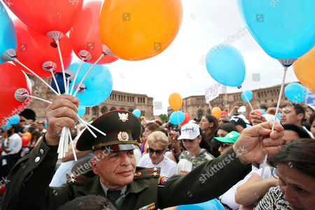 Stock Photo of An Armenian army officer hands out balloons during a rally in Republic Square in Yerevan, Armenia, . The Armenian opposition leader Nikol Pashinian, who is nearly certain to become the country's prime minister says he will not seek political revenge in the wake of the past month of tensions. Pashinian, who led weeks of protests that attracted tens of thousands of people and forced Serzh Sargsyan to resign as premier, is expected to be chosen prime minister by parliament on Tuesday