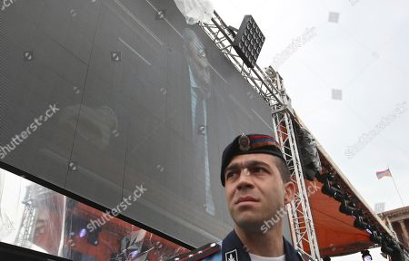 An Armenian police officer stands under a large screen, showing the opposition lawmaker Nikol Pashinian speaking in parliament during a rally in Republic Square in Yerevan, Armenia, . The Armenian opposition who is nearly certain to become the country's prime minister says he will not seek political revenge in the wake of the past month of tensions. Pashinian, who led weeks of protests that attracted tens of thousands of people and forced Serzh Sargsyan to resign as premier, is expected to be chosen prime minister by parliament on Tuesday