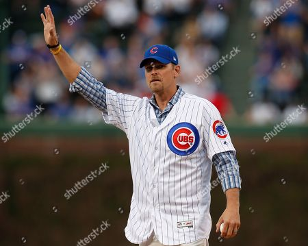 Stock Picture of Former Chicago Cubs pitcher Kerry Wood waves to the crowd before throwing out the ceremonial first pitch for a baseball game between the Cubs and the Miami Marlins, in Chicago