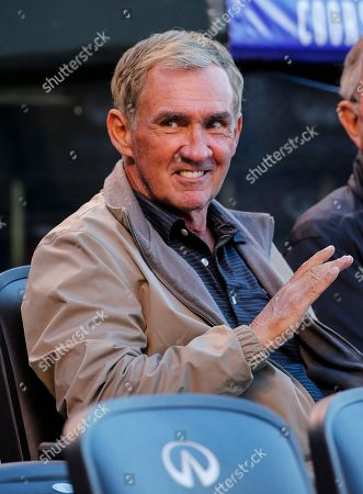 Former NFL coach Mike Shanahan looks on during the first inning of a baseball game between the Colorado Rockies and the Los Angeles Angels, in Denver