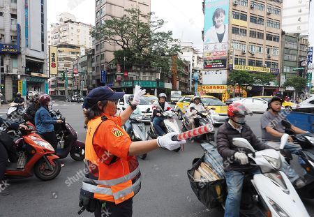 A policewoman directs traffic in Taipei, Taiwan, 09 May 2018. On 09 May, former president Ma Ying-jeou said that Taiwan's seeking independence is unnecessary and impossible. The challenge facing China and Taiwan is to get the two sides achieve peaceful reunification. Ma said that the German formula can be the best referemce because the two Germanies were reunified in 1990 on the basis of long-time reconcilliation.