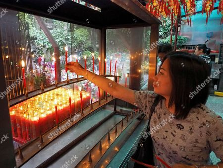 A woman lights a candle in a Taoist temple in Taipei, Taiwan, 09 May 2018. Former president Ma Ying-jeou on 09 May 2018 said that Taiwan's seeking independence is unnecessary and impossible. The challenge facing China and Taiwan is to get the two sides achieve peaceful reunification. Ma said that the German formula can be the best referemce because the two Germanies were reunified in 1990 on the basis of long-time reconcilliation.