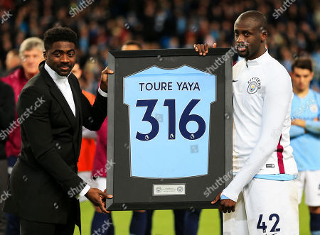 Yaya Toure of Manchester City is presented with a framed shirt by his brother Kolo Toure after his final match at the Etihad Stadium