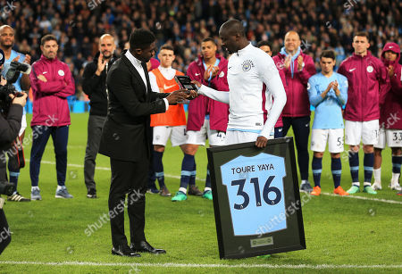 Yaya Toure of Manchester City is presented with a plaque and framed shirt by his brother Kolo Toure after his final match at the Etihad Stadium