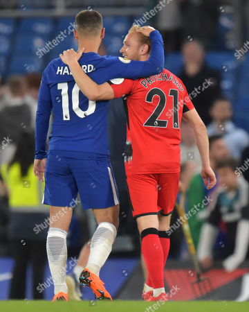 Alex Pritchard of Huddersfield Town talks with Eden Hazard of Chelsea as they eave the field.