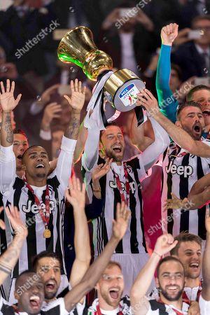 Douglas Costa de Souza of Juventus and Claudio Marchisio of Juventus and Andrea Barzagli of Juventus lift the trophy