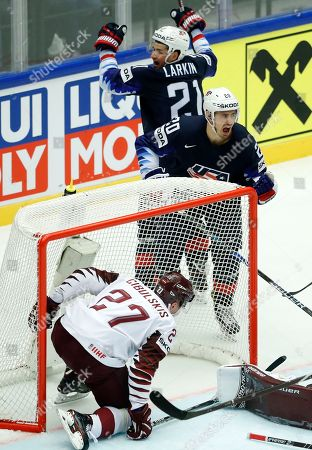 Latvia's Oskars Cibulskis, front, ends up in the net as Chris Kreider, center, of the United States celebrates with teammate Dylan Larkin, back, after scoring his sides first goal during the Ice Hockey World Championships group B match between United States and Latvia at the Jyske Bank Boxen arena in Herning, Denmark