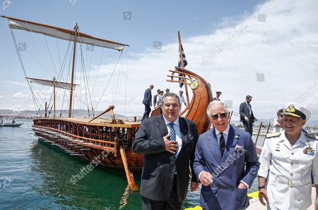 Prince Charles and Defence Minister Panos Kammenos (L) stand next to trireme replica Olympias in Floisvos near Athens