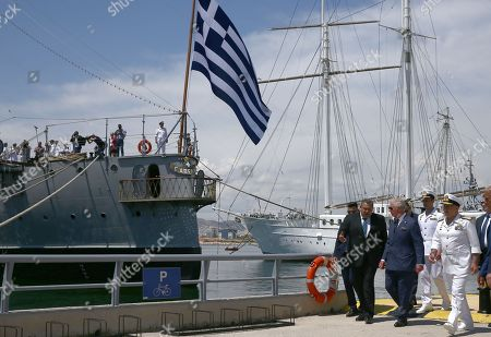 Prince Charles and Minister of Defence Panos Kammenos (L) walk beside Battle Ship G. Averof in Floisvos near Athens