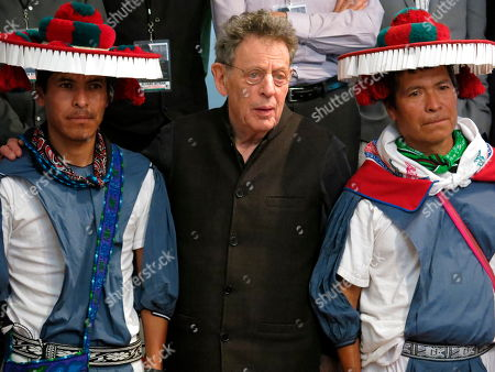 U.S. composer Philip Glass, center, stands with Wirrarika musicians Daniel Medina de la Rosa, left, and Erasmo Medina Medina during a press conference in Mexico City, . Glass will present a series of concerts in Mexico's Fine Arts Palace including the Mexican debut of his Toltec Symphony and a collaboration with Wirrarika musicians