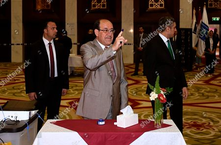 Former Iraqi Prime Minister Nouri al-Maliki, center, shows his ink-stained finger after casting his vote in the country's parliamentary elections in the heavily fortified Green Zone in Baghdad, Iraq, . Polls opened across Iraq on Saturday in the first national election since the declaration of victory over the Islamic State group