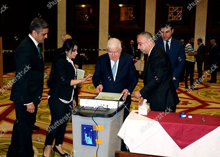 Iraqi President Fuad Masum, center, casts his vote in the country's parliamentary elections in the heavily fortified Green Zone in Baghdad, Iraq, . Polls opened across Iraq on Saturday in the first national election since the declaration of victory over the Islamic State group