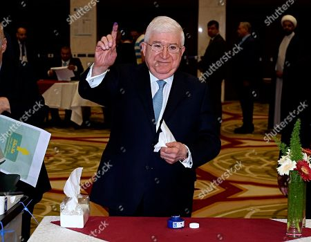 Iraqi President Fuad Masum shows his ink-stained finger after casting his vote in the country's parliamentary elections in the heavily fortified Green Zone in Baghdad, Iraq, . Polls opened across Iraq on Saturday in the first national election since the declaration of victory over the Islamic State group