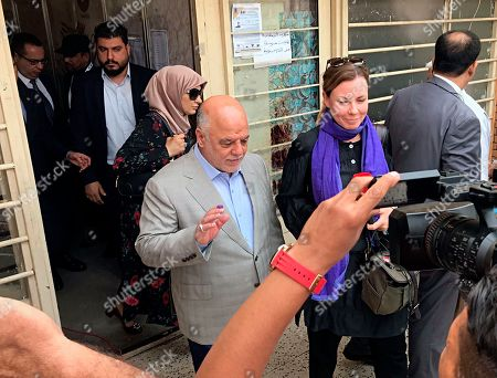 Iraq Prime Minister Haider al-Abadi, center, leaves a polling station after casting his ballot in the country's parliamentary elections in Baghdad, Iraq, . Polls opened across Iraq on Saturday in the first national election since the declaration of victory over the Islamic State group