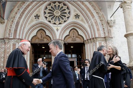 Colombian President Juan Manuel Santos, second from left, shakes hands with Cardinal Agostino Vallini as his wife Maria Clemencia Rodriguez, right, is greeted by Father Mauro Gambetti upon their arrival outside Assisi's Basilica, Italy, . German Chancellor Angela Merkel and Colombian President Juan Manuel Santos arrived in Assisi to receive the Lamp of Peace award