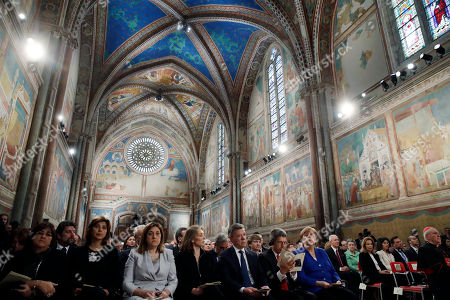 President Juan Manuel Santos, center, his wife Maria Clemencia Rodriguez, fourth from left, German Chancellor Angela Merkel, right, flanked by her husband Joachim Sauer listen to a welcome speech during a ceremony inside Assisi's Basilica, Italy, . Merkel and Santos arrived in Assisi to receive the Lamp of Peace award