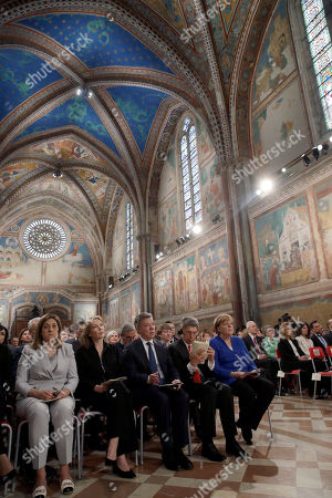 President Juan Manuel Santos, center, his wife Maria Clemencia Rodriguez, second from left, German Chancellor Angela Merkel, right, flanked by her husband Joachim Sauer listen to a welcome speech during a ceremony inside Assisi's Basilica, Italy, . Merkel and Santos arrived in Assisi to receive the Lamp of Peace award