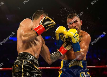 Stock Photo of Jorge Linares,left, of Venezuela, connects with Vasiliy Lomachenko, of Ukraine, during their WBA lightweight championship boxing match, in New York